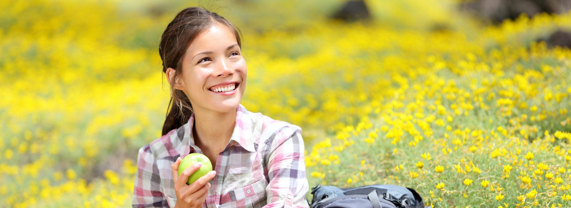 Eine Frau isst einen Apfel auf einer gelben Blumenwiese