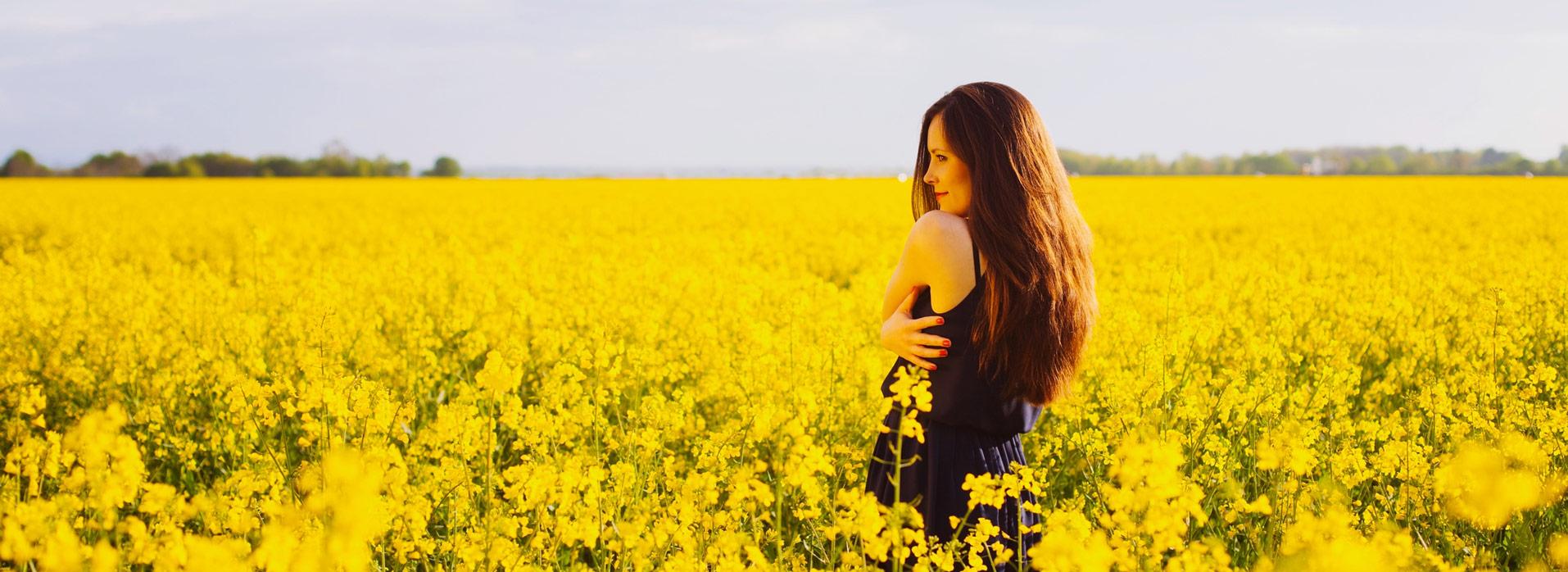 Eine Frau steht in einer gelben Blumenwiese