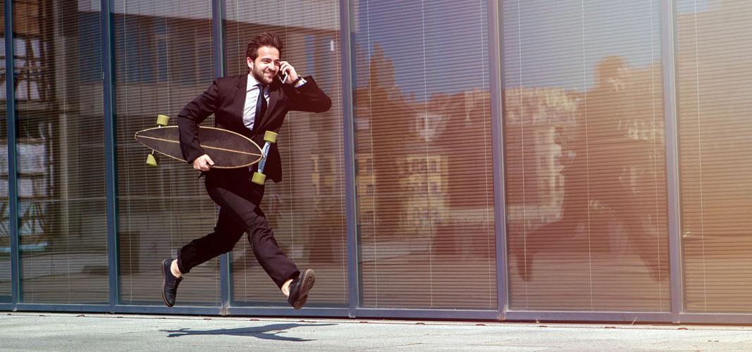 Rennender Geschäftsmann mit Longboard unter dem Arm