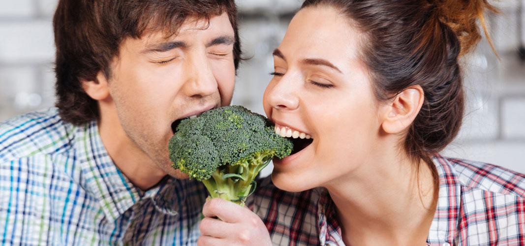 Ein Paar beißt zusammen in einen Brokolli
